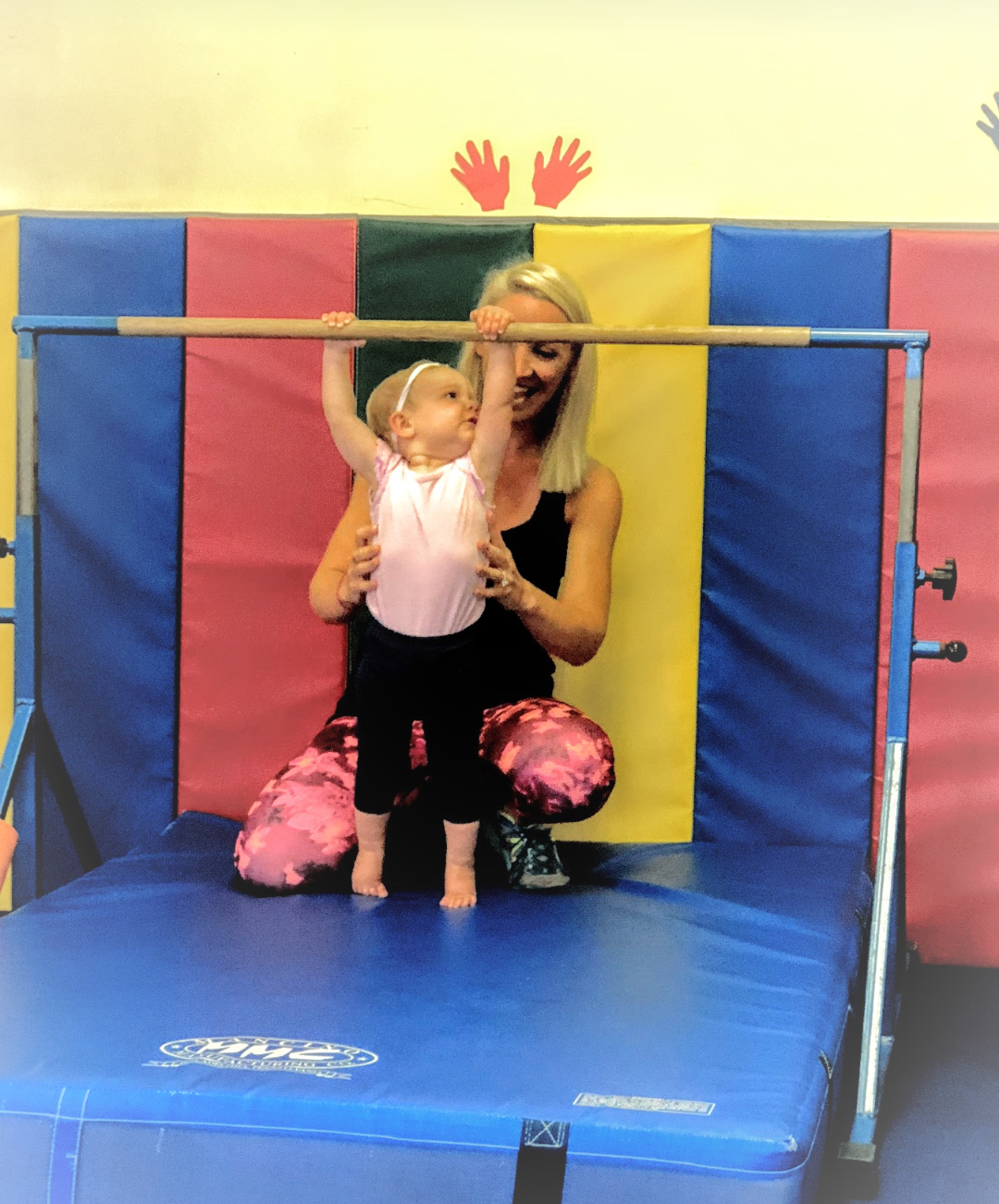 Toddler on miniature gymnastics bars with mom
