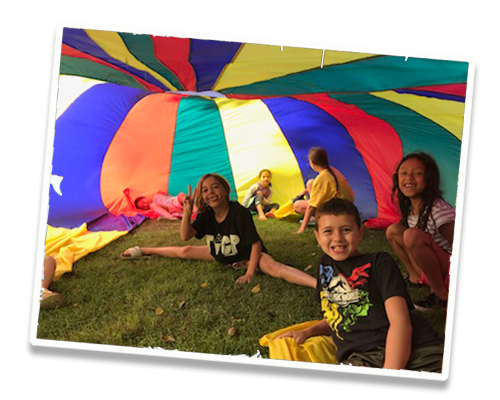 Kids on grass under a rainbow parachute at summer camp