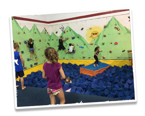 Kids climbing on rock wall over foam cube pit