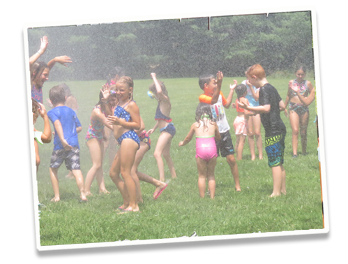 Kids playing in grass under firehose sprinkler