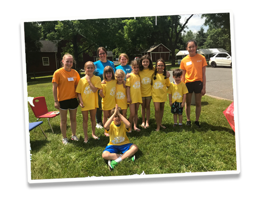 Summer Camp Kids group photo of kids with orange and yellow shirts